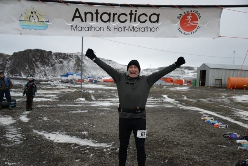 Truman Smith under Antarctica banner finishing a marathon