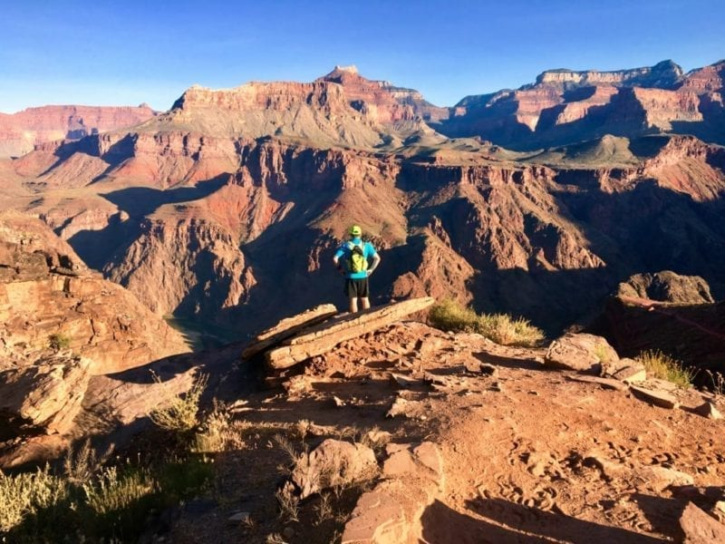 Runner standing atop the Grand Canyon