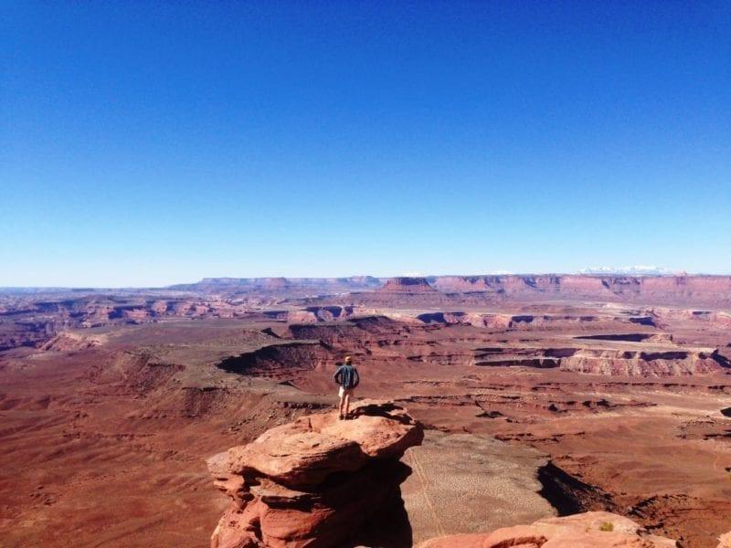 Person standing atop desert rock.