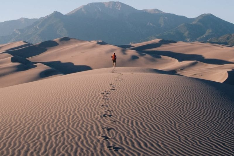 Person walking in the desert towards a far off mountain.