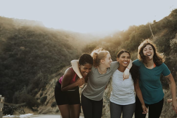 group of women on hike holding each other arm and arm and over the shoulders while laughing and walking - Prevent & Avoid Chafing - Body Glide