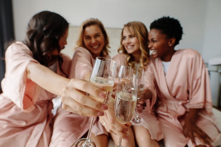 women in matching robes laughing and smiling while sitting on bed celebrating with glasses of champagne- Wedding Day Chafing - Body Glide