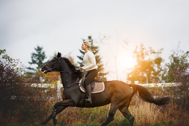 Blonde woman on horseback riding through a field while sun sets in background - Chafing from Horseback Riding - Body Glide