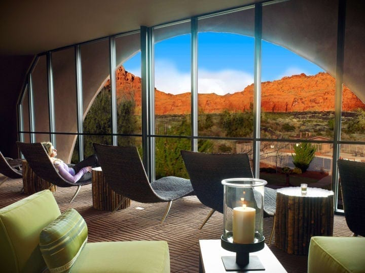 Woman lounging on chair in front of windows looking at mountains