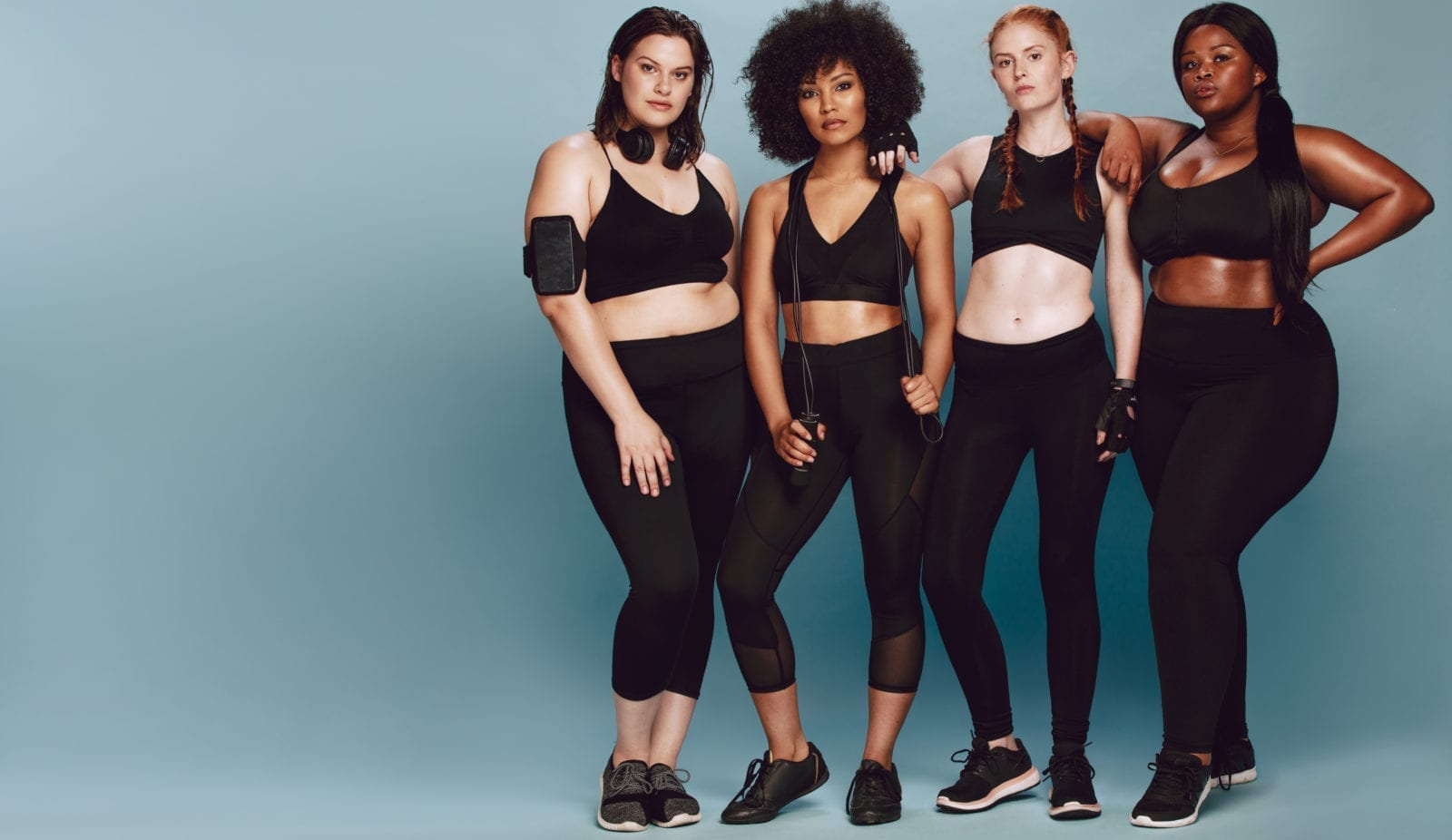 Full length of multi-ethnic women with in sportswear standing together over grey background. Three women of different race, figure type and size in fitness clothing.