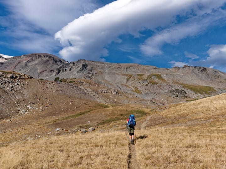 Person hiking through a mountainous landscape.