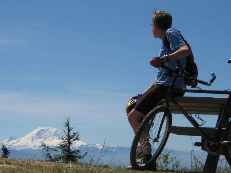 Man leaning against bike up against a picnic table with Mount Rainier in the background.