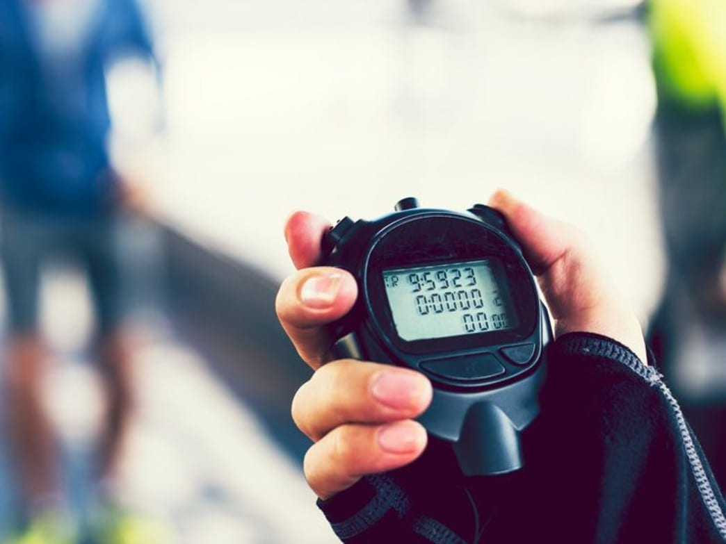Person holding a stopwatch timing a workout