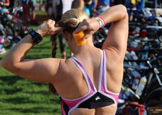 Woman in swimsuit putting Body Glide Sun balm on the back of her neck before a triathlon.